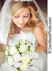 Attractive bride with wedding bouquet of roses. Beauty makeup