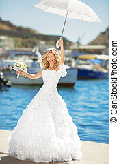 Beautiful smiling bride in wedding dress with white umbrella posing over seafront, outdoor bridal portrait