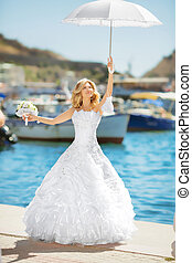 Beautiful bride in wedding dress with white umbrella posing over seafront, outdoor bridal portrait