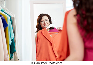 happy plus size woman with shirt at mirror - clothing,...
