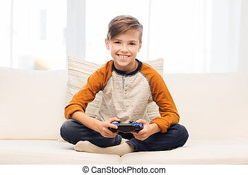 happy boy with joystick playing video game at home -...