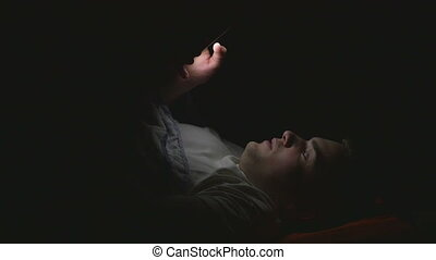 Attractive young man using a smart phone in bed