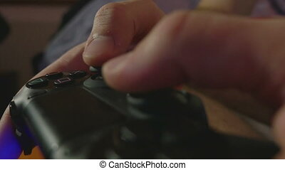 Close-up of man hands playing console games with a...