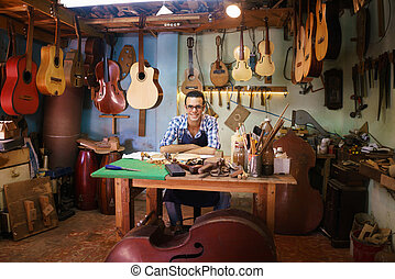 Portrait Of Happy Artisan Lute Maker In Guitar Shop Smiling...