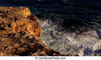 Colorful cliff line with deep blue ocean and breaking waves