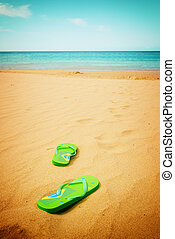 green sandals on sandy beach - green sandals left on the...