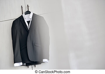 Black suit hanged to a wood closet in natural light