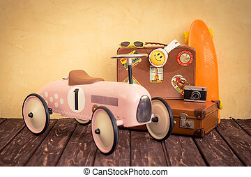 Vintage toy car and suitcase. Travel and summer vacation...