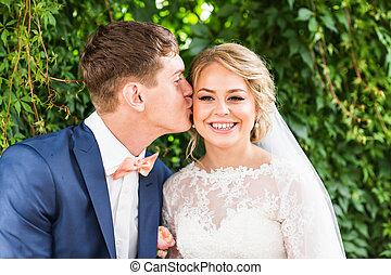 Young wedding couple enjoying romantic moments outdoors -...