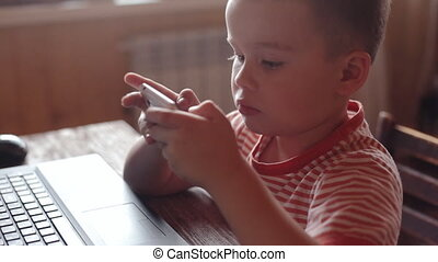 Little boy uses smartphone at home - Little boy on...