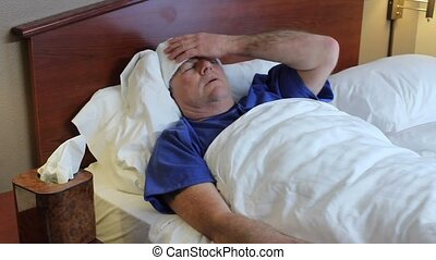 Bedridden mature man - A mature man with a bad cold lying in...