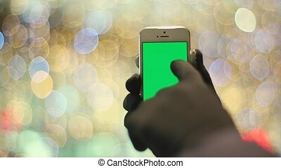 Man Using Smartphone With Green Screen in Background Light....