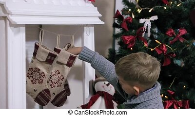 A boy looking gifts toes by the fireplace, white Room with...