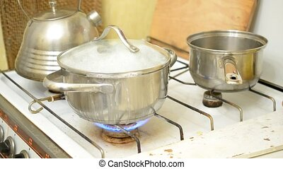 Food boiling over in saucepan - Food boiling over in...