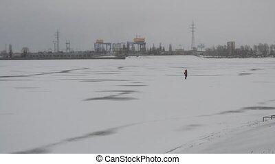 Unfocused video of winter fisherman walking on frozen lake -...
