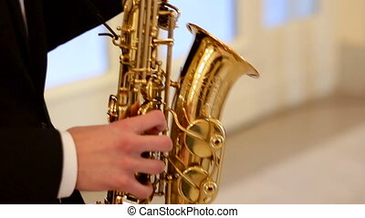 man plays the saxophone in a black suit