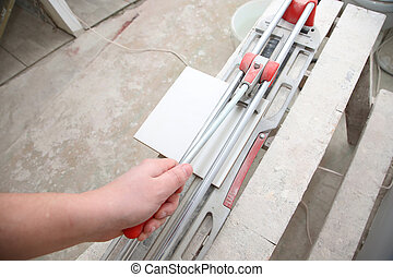 ceramic tile cutter with tile - Worker holds the handle of...