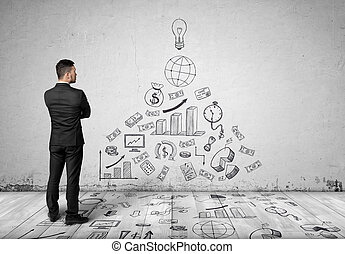 Young businessman in suit, standing front of concrete wall with business sketches on it.