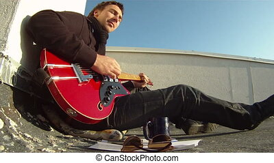 Musician with a guitar on the roof - The musician sits on...