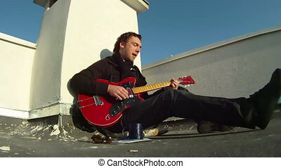 A musician plays the guitar - The musician sits on the roof...
