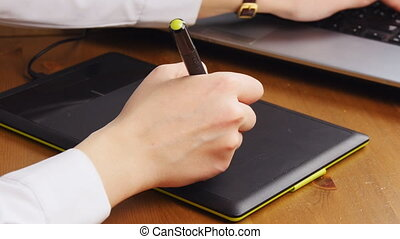Female hand drawing on the graphic tablet in the office,...