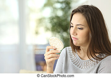 Girl disgusted looking a dietetic cookie. Bad diet concept