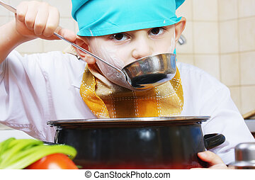 Testing food - Little cook in green cap testing food from...