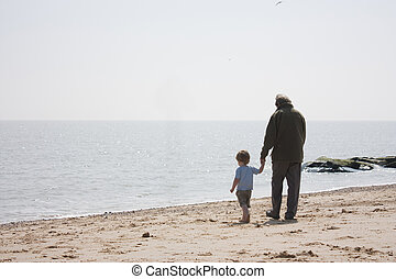 grandad and grandson on the beach - holding hands...