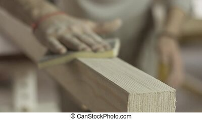 Professional carpenter polish wooden board surface by special sponge. Furniture