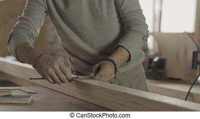 Professional locksmith measures wooden board by special ruler. Furniture