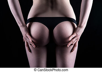 Woman in black panties touching buttocks on black background