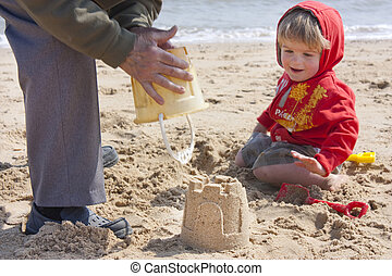 sandcastle building - building a sandcastle on the beach,...