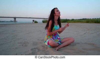 Cinemagraph of girl sitting on sand and dancing