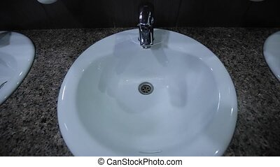 A man approaches the tap opens the tap, the water begins to...