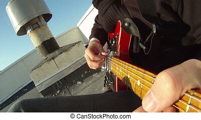 Musician wrote a song - Man plays the guitar on the roof....