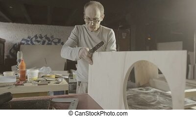 Professional woodworker connects two wooden polished board. Furniture. Hammer