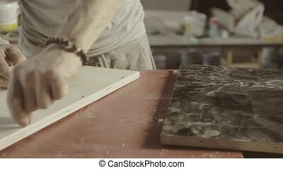 Professional woodworker connects two wooden board. Process of assembly furniture