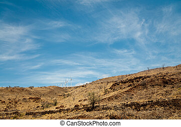 Row of wind turbines on a dry hill