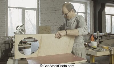 Professional carpenter connects two wooden polished board. Furniture. Process