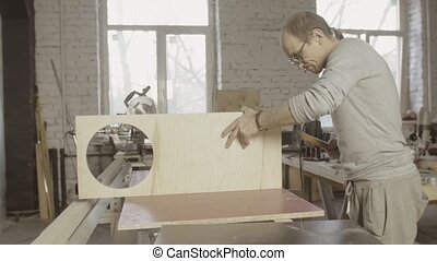 Professional carpenter connects two wooden board. Hammer. Process of assembly