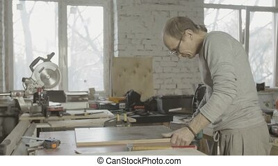 Professional woodworker polish edge of wooden board by belt...