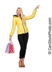 Caucasian woman in yellow jacket holding plastic bags...