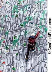 Boy climber on a wall - Boy climbing up a wall in an...