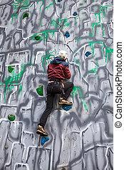Boy climber on a wall - Boy climbing up a wall in an...