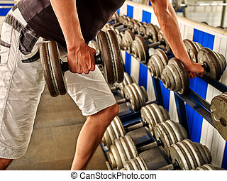 Man working his arms with dumbbells at gym He lifting...