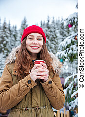 Woman drinking coffee near decorated christmas tree in...