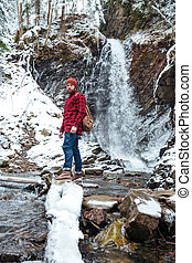 Man with backpack standing near waterfall at mountains in winter