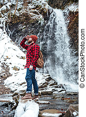 Handsome berded man walking near waterfall at mountains in winter