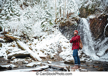 Pensive bearded man stading near waterfall at mountains in winter