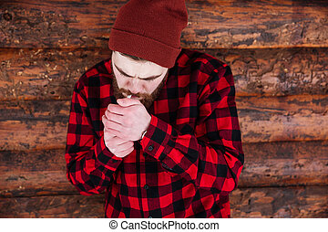 Young man smoking on wooden background